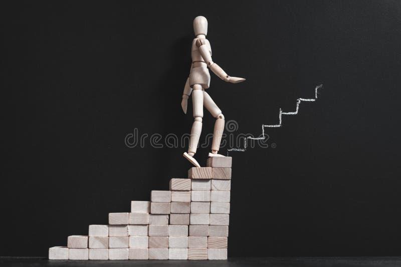 Ξύλινο άτομο φιλοδοξίας σταδιοδρομίας που αναρριχείται στην κιμωλία σκαλοπατιών στοκ εικόνα