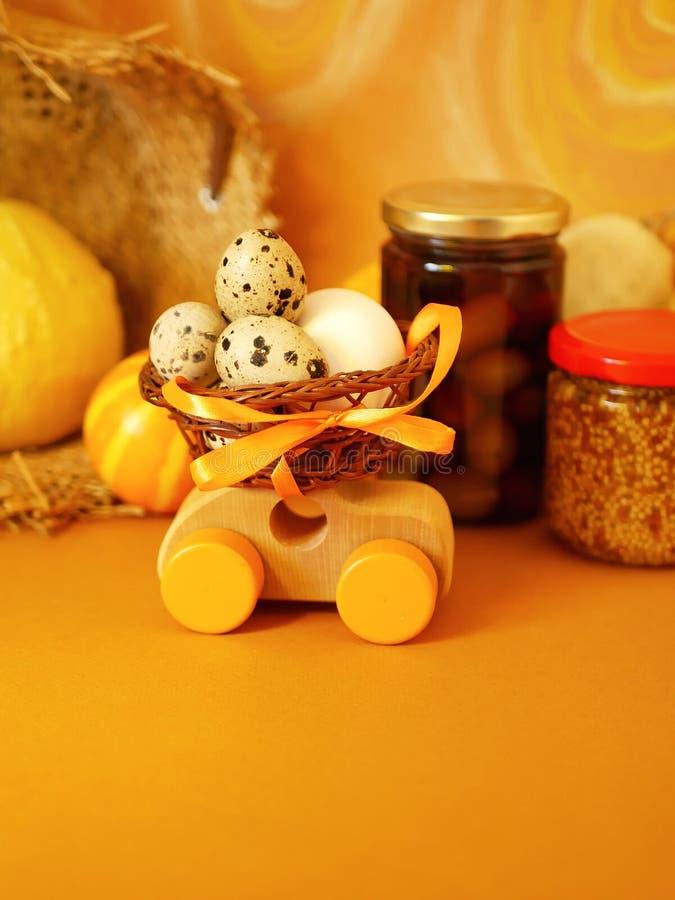Ξύλινο αυτοκίνητο παιχνιδιών με ένα καλάθι των αυγών ορτυκιών σε ένα φωτεινό κίτρινο υπόβαθρο που χρωματίζεται στις κρητιδογραφίε στοκ εικόνα με δικαίωμα ελεύθερης χρήσης