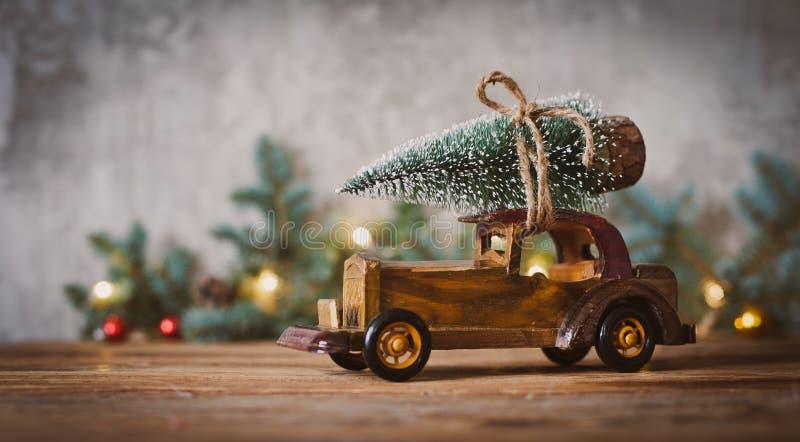 Ξύλινο αυτοκίνητο παιχνιδιών με το χριστουγεννιάτικο δέντρο στη στέγη σε έναν ξύλινο πίνακα στοκ φωτογραφίες