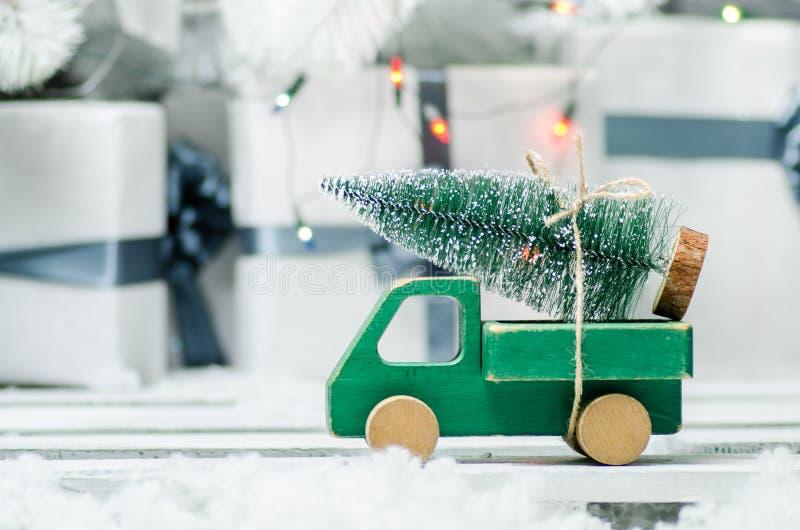 Ξύλινο αυτοκίνητο παιχνιδιών που φέρνει ένα χριστουγεννιάτικο δέντρο στο λαμπρό υπόβαθρο φω'των στοκ εικόνες