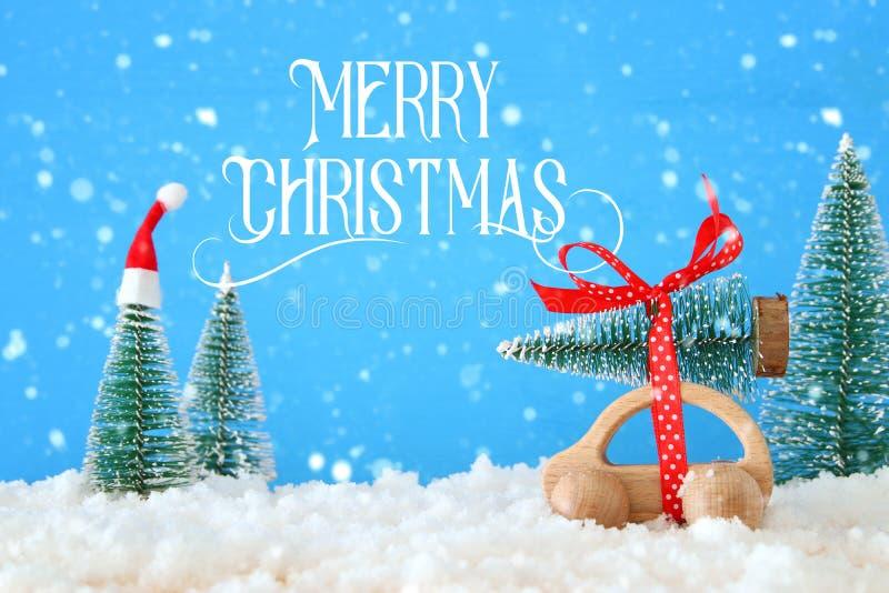 Ξύλινο αυτοκίνητο που φέρνει ένα χριστουγεννιάτικο δέντρο με το καπέλο santa μπροστά από το μπλε υπόβαθρο στοκ φωτογραφία