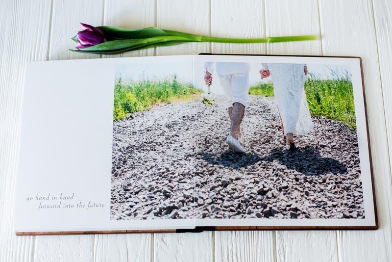 Ξύλινο βιβλίο γαμήλιων φωτογραφιών ευτυχείς νεολαίες αγάπης ζευγών Περπάτημα νυφών και νεόνυμφων της ημέρας γάμου στοκ εικόνες