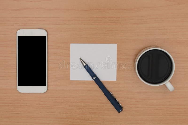 Ξύλινο γραφείο με το κενούς έξυπνους τηλέφωνο, τον καφέ, τη σημείωση εγγράφου και τη μάνδρα στοκ φωτογραφίες με δικαίωμα ελεύθερης χρήσης