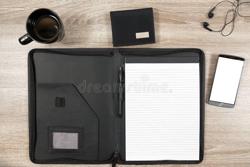 Ξύλινο γραφείο με το smartphone, ακουστικά, πορτοφόλι, κούπα καφέ και στοκ εικόνα