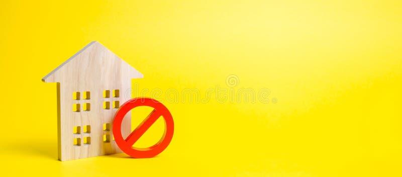 Ξύλινο ειδώλιο σπιτιών και ένα κόκκινο σύμβολο αριθ. ή απαγόρευση απρόσιτο ή έλλειψη κατοικίας Δεν υπάρχει καμία ευκαιρία να αγορ στοκ εικόνα με δικαίωμα ελεύθερης χρήσης
