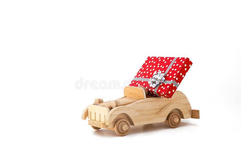 Ξύλινο εκλεκτής ποιότητας αυτοκίνητο παιχνιδιών με ένα κόκκινο κιβώτιο, δώρο σε ένα άσπρο υπόβαθρο στοκ φωτογραφίες με δικαίωμα ελεύθερης χρήσης
