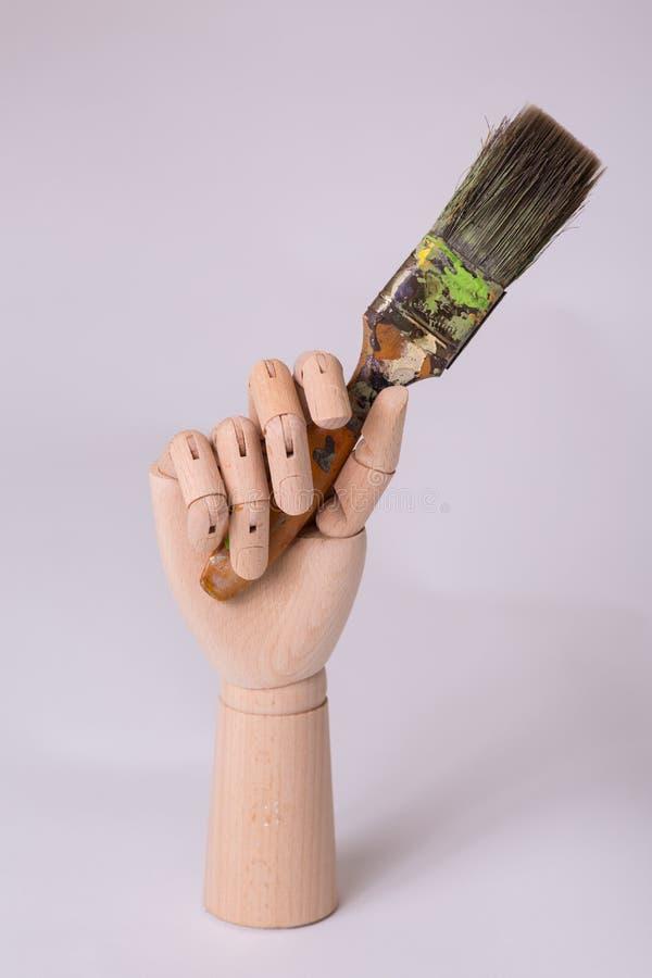 Ξύλινο ενωμένο χέρι ανδρείκελων που κρατά ψηλά έναν πυροβολισμό στούντιο βουρτσών τέχνης ζωγράφων στοκ εικόνα