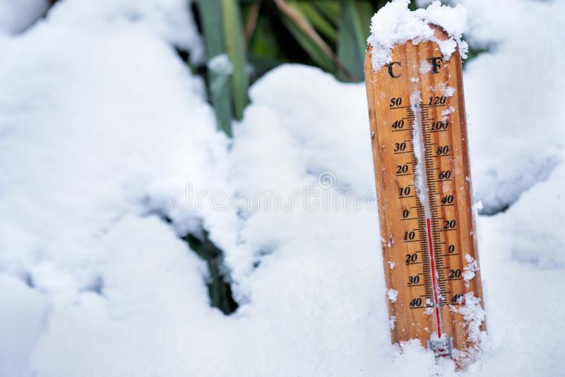 Ξύλινο θερμόμετρο που στέκεται πάνω σε μερικώς κατεψυγμένο χιόνι στοκ εικόνες