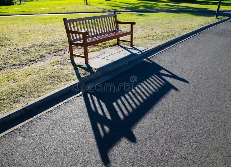 Ξύλινο κάθισμα πάγκων στον κήπο με τη σκιά του σε αργά το απόγευμα στοκ εικόνες