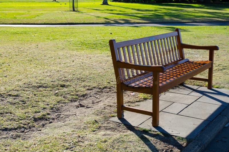 Ξύλινο κάθισμα πάγκων στον κήπο σε αργά το απόγευμα στοκ εικόνα με δικαίωμα ελεύθερης χρήσης