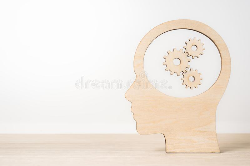 Ξύλινο κεφάλι σκιαγραφιών ατόμων με gearwheel στοκ εικόνα