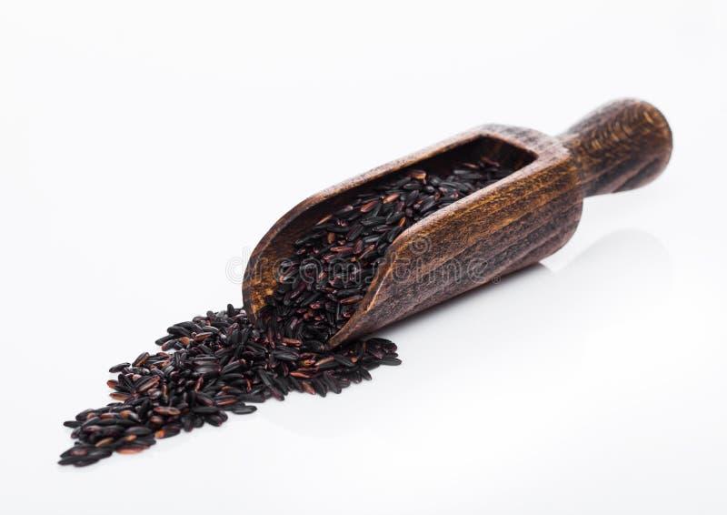 Ξύλινο κουτάλι του ακατέργαστου οργανικού μαύρου ρυζιού της Αφροδίτης στο άσπρο υπόβαθρο r στοκ εικόνες
