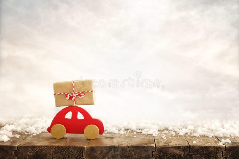 Ξύλινο κόκκινο αυτοκίνητο που φέρνει ένα δώρο Χριστουγέννων πέρα από το χιόνι στοκ εικόνες