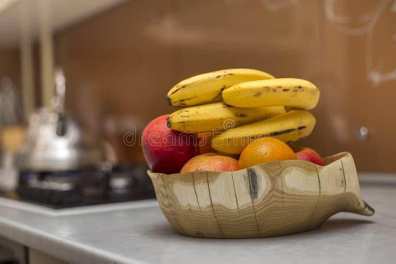 Ξύλινο κύπελλο πιάτων με τα φρέσκα εύγευστα yummy μήλα φρούτων μπανάνες και πορτοκάλι στον άσπρο πίνακα κουζινών θολωμένο στο φως στοκ φωτογραφία με δικαίωμα ελεύθερης χρήσης