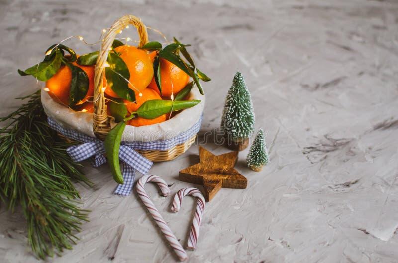 Ξύλινο μανταρίνι καλαθιών με τα φύλλα και φω'τα, Tangerine πορτοκάλι στα γκρίζα επιτραπέζιου υποβάθρου ντεκόρ έτους Χριστουγέννων στοκ φωτογραφίες με δικαίωμα ελεύθερης χρήσης