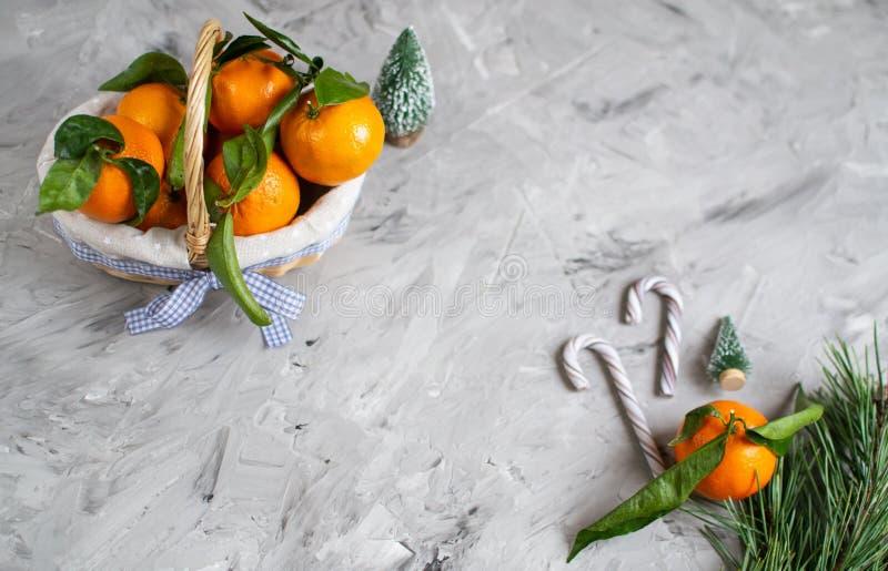 Ξύλινο μανταρίνι καλαθιών με τα φύλλα και φω'τα, Tangerine πορτοκάλι στα γκρίζα επιτραπέζιου υποβάθρου ντεκόρ έτους Χριστουγέννων στοκ εικόνες με δικαίωμα ελεύθερης χρήσης