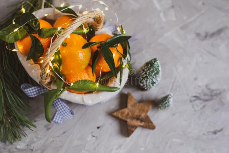 Ξύλινο μανταρίνι καλαθιών με τα φύλλα και φω'τα, Tangerine πορτοκάλι στα γκρίζα επιτραπέζιου υποβάθρου ντεκόρ έτους Χριστουγέννων στοκ φωτογραφίες