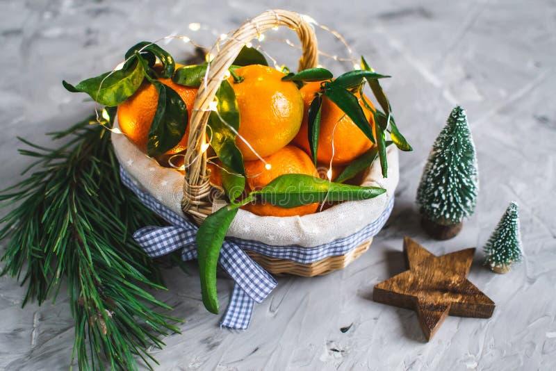 Ξύλινο μανταρίνι καλαθιών με τα φύλλα και φω'τα, Tangerine πορτοκάλι στα γκρίζα επιτραπέζιου υποβάθρου ντεκόρ έτους Χριστουγέννων στοκ εικόνες
