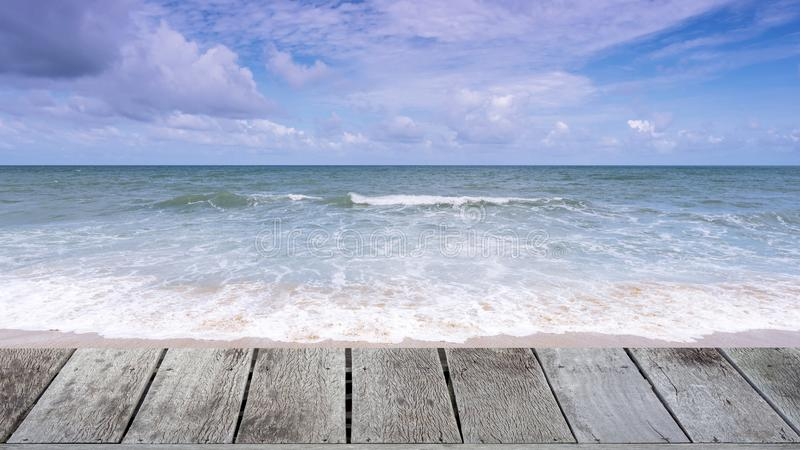 Ξύλινο πάτωμα στην όμορφη τροπική αμμώδη παραλία με το μπλε υπόβαθρο ωκεανών και μπλε ουρανού και κύμα που συντρίβει στην αμμώδη  στοκ εικόνα