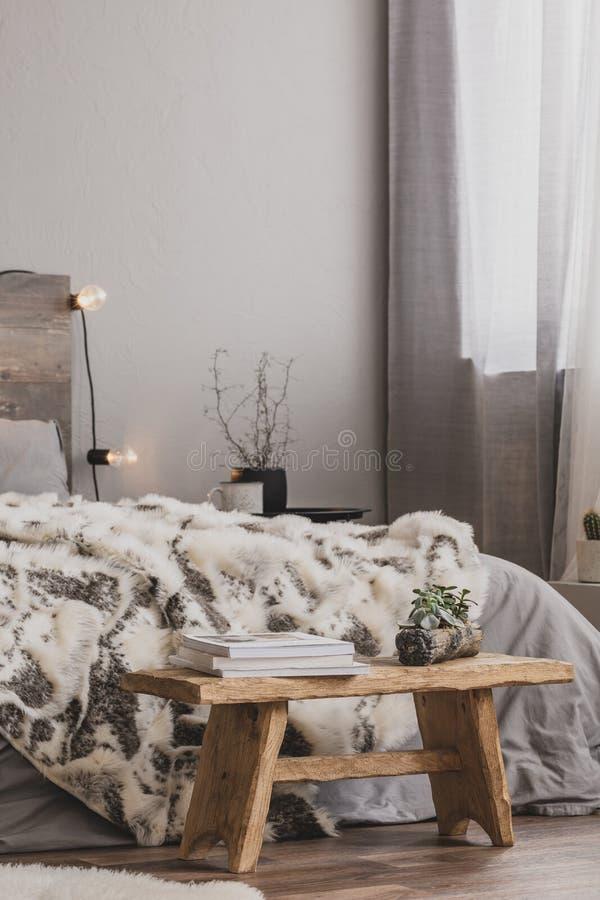 Ξύλινο παγκάκι με βιβλία και λουλούδια στο πόδι του κρεβατιού με γκρι στρωμνή και ζεστή κουβέρτα στοκ φωτογραφία