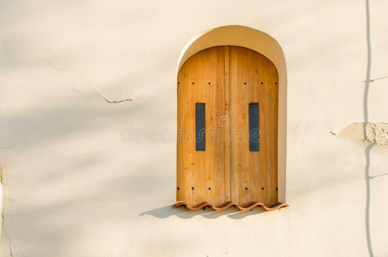 Ξύλινο παράθυρο στον ελαφρύ τοίχο με το κλειστό παραθυρόφυλλο κατά τη διάρκεια της ηλιόλουστης ημέρας στοκ εικόνες