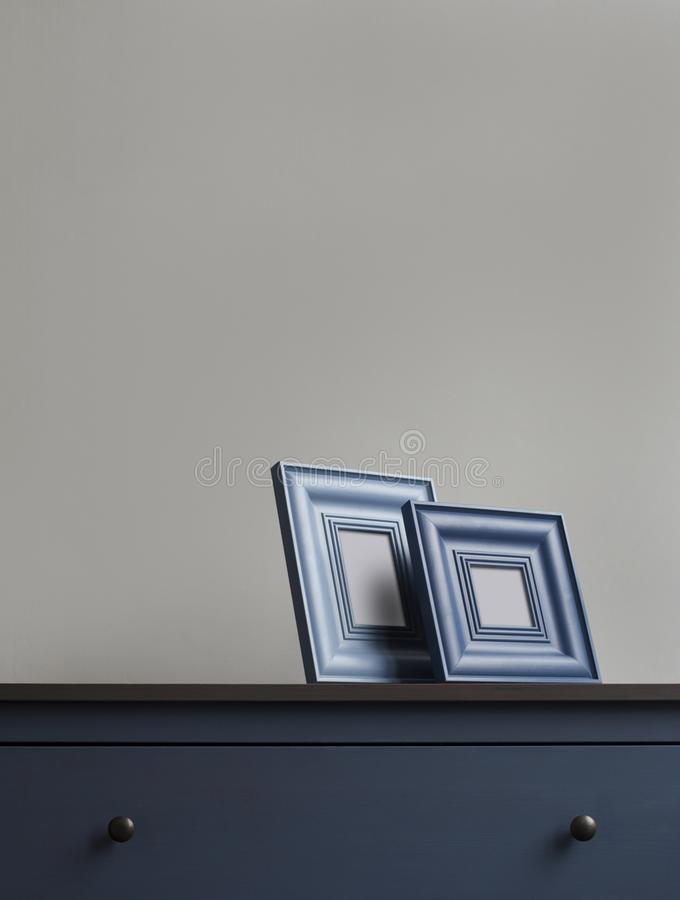 Ξύλινο πλαίσιο εικόνων δύο στο μπλε στήθος των συρταριών στοκ εικόνες