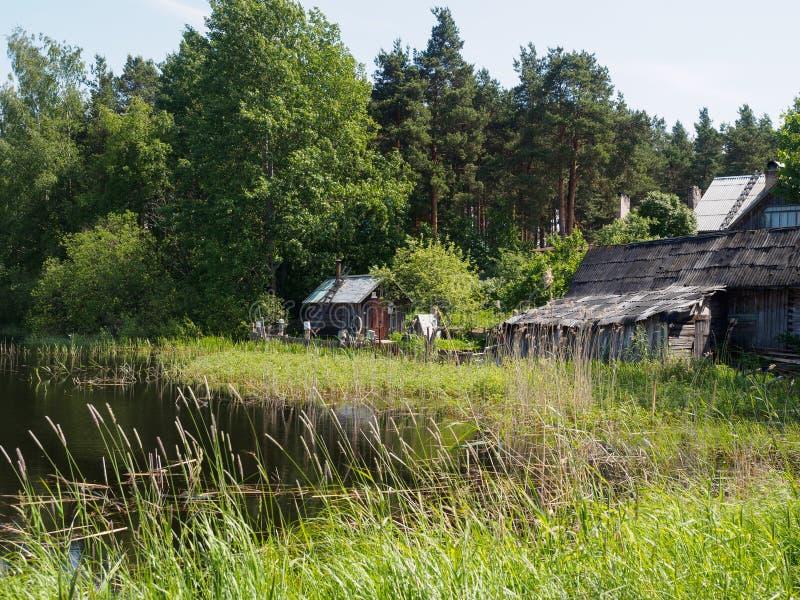 Ξύλινο σπίτι από τον ποταμό στη χλόη στοκ εικόνες