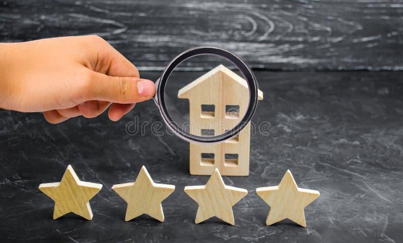 Ξύλινο σπίτι και τέσσερα αστέρια σε ένα γκρίζο υπόβαθρο Εκτίμηση των σπιτιών και της ιδιωτικής ιδιοκτησίας Αγορά και πώληση, που  στοκ φωτογραφία με δικαίωμα ελεύθερης χρήσης