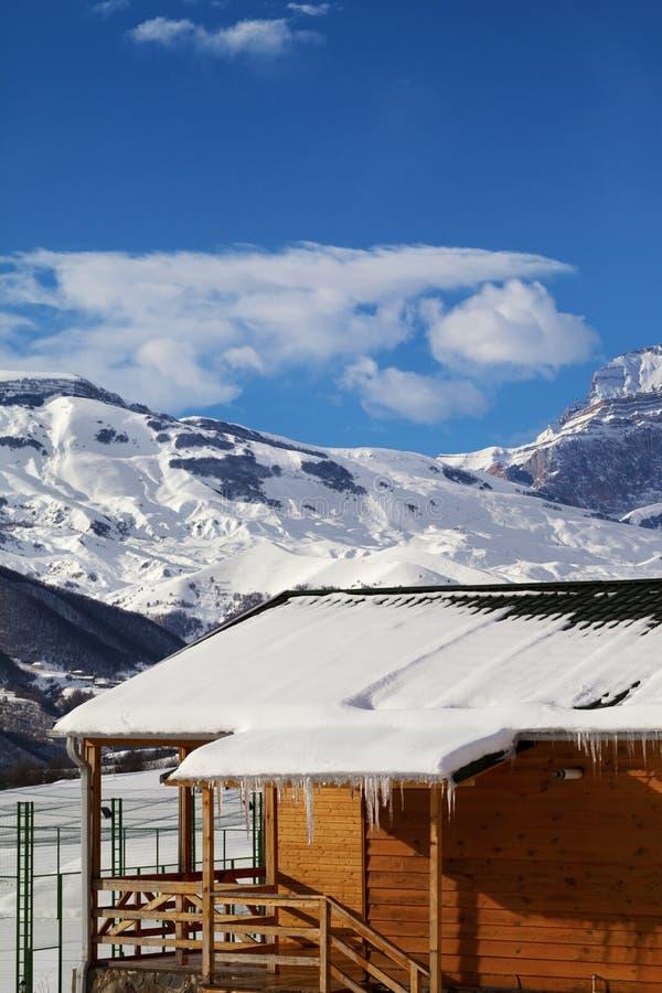 Ξύλινο σπίτι με τη χιονώδη στέγη και παγάκια στα χειμερινά βουνά χιονιού στοκ εικόνα