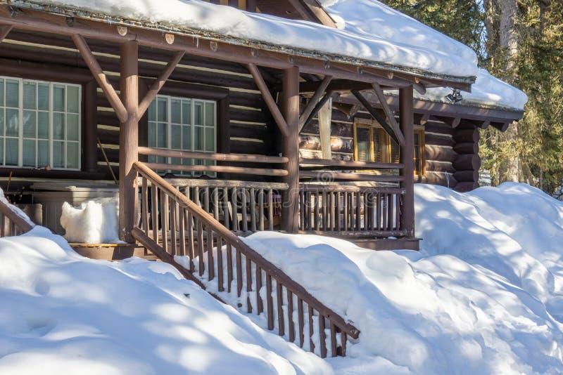 ξύλινο σπίτι που καλύπτεται στο χιόνι στα πρόωρα ξύλα Αλμπέρτα Καναδάς άνοιξη στοκ εικόνες