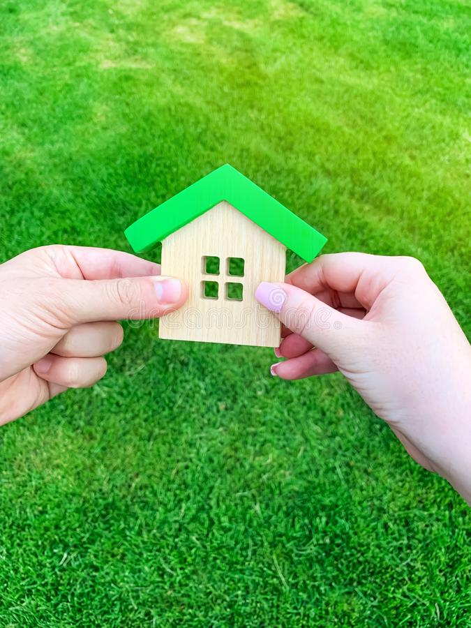 Ξύλινο σπίτι στο χέρι μιας νέας οικογένειας Αγορά ενός σπιτιού σε ένα ενυπόθηκο δάνειο E Φιλικό σπίτι Eco Κυβέρνηση στοκ εικόνα με δικαίωμα ελεύθερης χρήσης