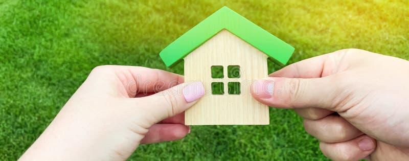Ξύλινο σπίτι στο χέρι μιας νέας οικογένειας Αγορά ενός σπιτιού σε ένα ενυπόθηκο δάνειο E Φιλικό σπίτι Eco Κυβέρνηση στοκ φωτογραφίες
