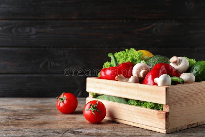 Ξύλινο σύνολο κλουβιών των φρέσκων ώριμων λαχανικών στον πίνακα στοκ εικόνα