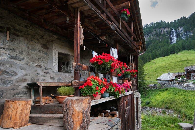 Ξύλινο σύνολο μπαλκονιών των κόκκινων λουλουδιών με τα βουνά και waterfull στο υπόβαθρο στοκ εικόνα με δικαίωμα ελεύθερης χρήσης