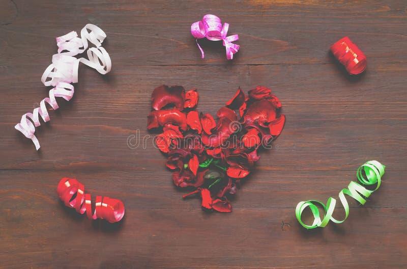 Ξύλινο υπόβαθρο με την καρδιά από τα πέταλα των ξηρών λουλουδιών και ομο στοκ φωτογραφία με δικαίωμα ελεύθερης χρήσης