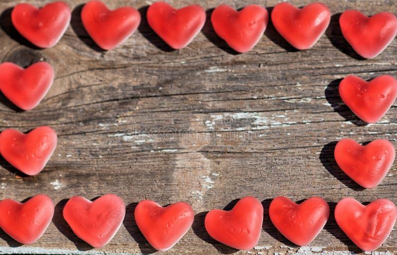 Ξύλινο υπόβαθρο με τις καρδιές μαρμελάδας στοκ φωτογραφία