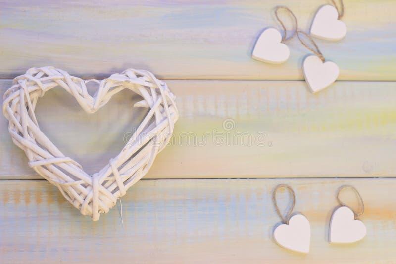 Ξύλινο υπόβαθρο του βαλεντίνου του ST με την υφαμένη καρδιά στοκ εικόνες
