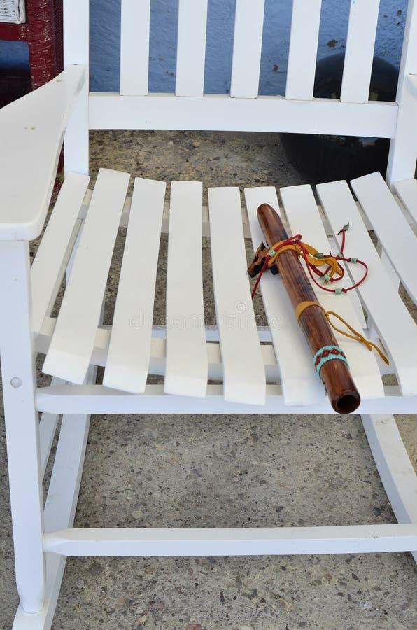 Ξύλινο φλάουτο αμερικανών ιθαγενών στο λίκνισμα του καθίσματος καρεκλών στοκ εικόνα με δικαίωμα ελεύθερης χρήσης
