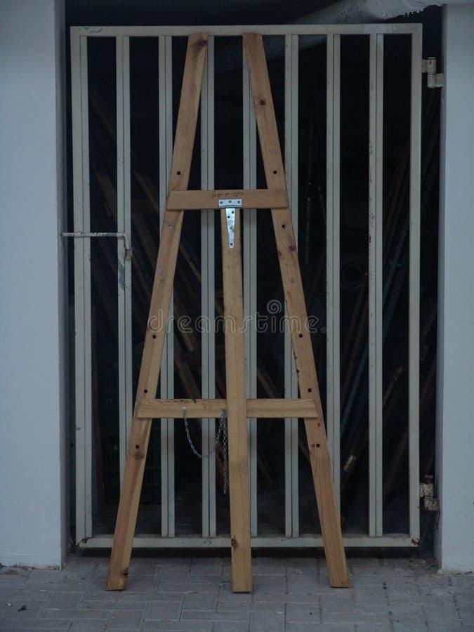 Ξύλινο ψηλό easel που στέκεται ενάντια σε μια πόρτα γκαράζ μετάλλων στο λευκό στοκ εικόνα