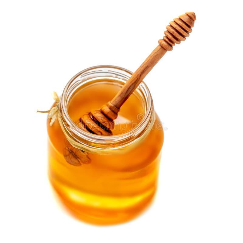 Ξύλινο dipper το στάζοντας βάζο μελιού και γυαλιού που απομονώνεται με στο μόριο στοκ εικόνα με δικαίωμα ελεύθερης χρήσης