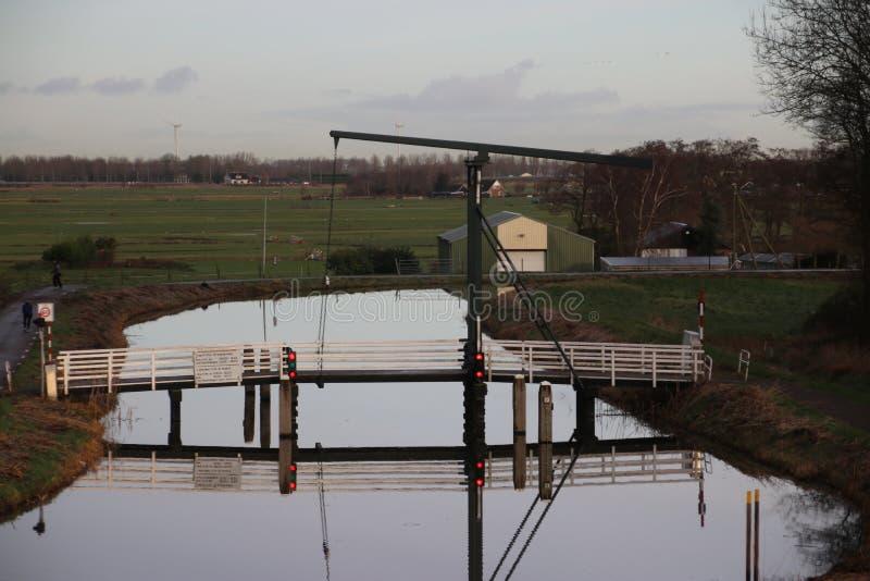 Ξύλινο drawbridge που απεικονίζει στην επιφάνεια νερού του καναλιού Zuidplaspolder δαχτυλιδιών σε Moordrecht στοκ φωτογραφία