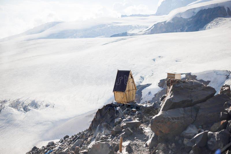Ξύλινο WC τουαλετών για τους ορειβάτες για το σπάσιμο στην άκρη του απότομου βράχου permafrost στους παγετώνες στο βουνό Elbrus στοκ εικόνες με δικαίωμα ελεύθερης χρήσης
