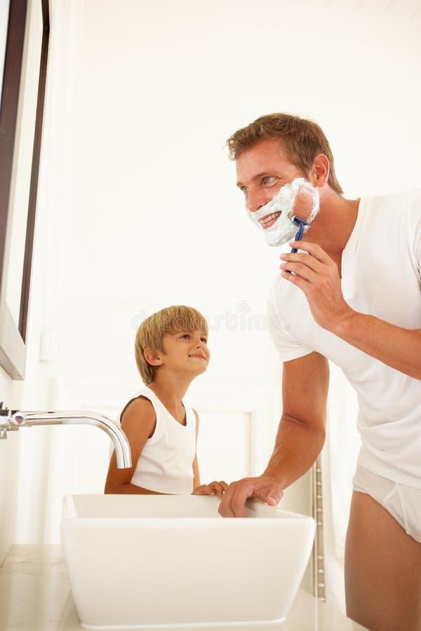 Ξύρισμα πατέρων προσοχής γιων στον καθρέφτη λουτρών στοκ φωτογραφία