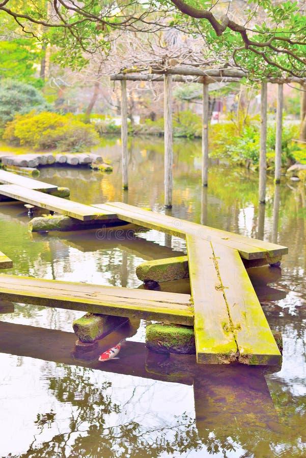 Ξύλινα γέφυρα σανίδων, yatsuhashi, και ψάρια κυπρίνων στον ιαπωνικό κήπο στοκ φωτογραφίες με δικαίωμα ελεύθερης χρήσης