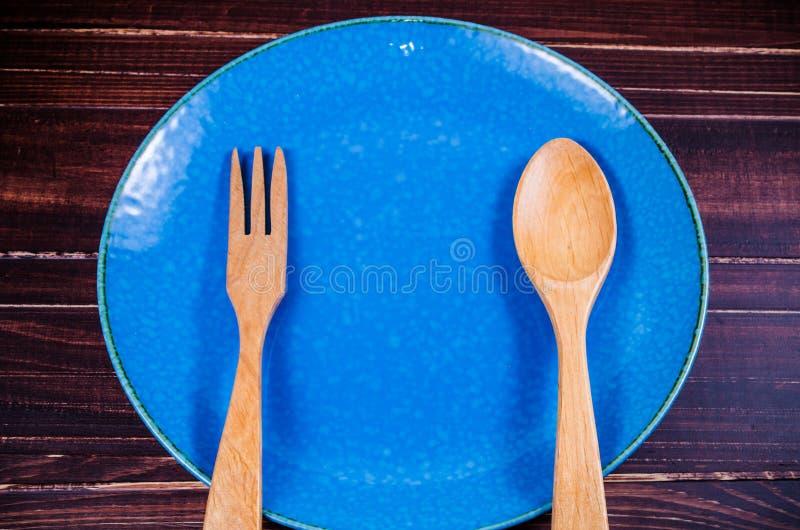 Ξύλινα κουτάλι και δίκρανο στο μπλε πιάτο στοκ εικόνα με δικαίωμα ελεύθερης χρήσης