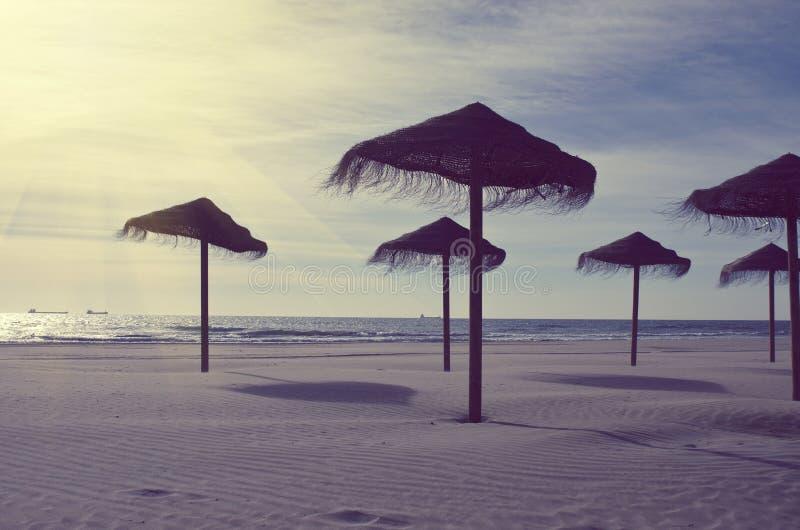 Ξύλινες σκιαγραφίες ομπρελών θαλάσσης στην παραλία θάλασσας Έννοια διακοπών στον εκλεκτής ποιότητας τόνο χρώματος στοκ εικόνες με δικαίωμα ελεύθερης χρήσης
