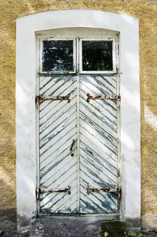 Ξύλινη άσπρη πόρτα με τις αρθρώσεις επεξεργασμένος-σιδήρου στοκ φωτογραφία