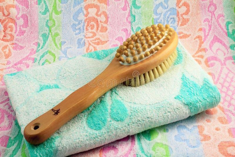 Ξύλινη βούρτσα με τη λαβή για το μασάζ ενός σώματος και μιας πετσέτας. στοκ φωτογραφία