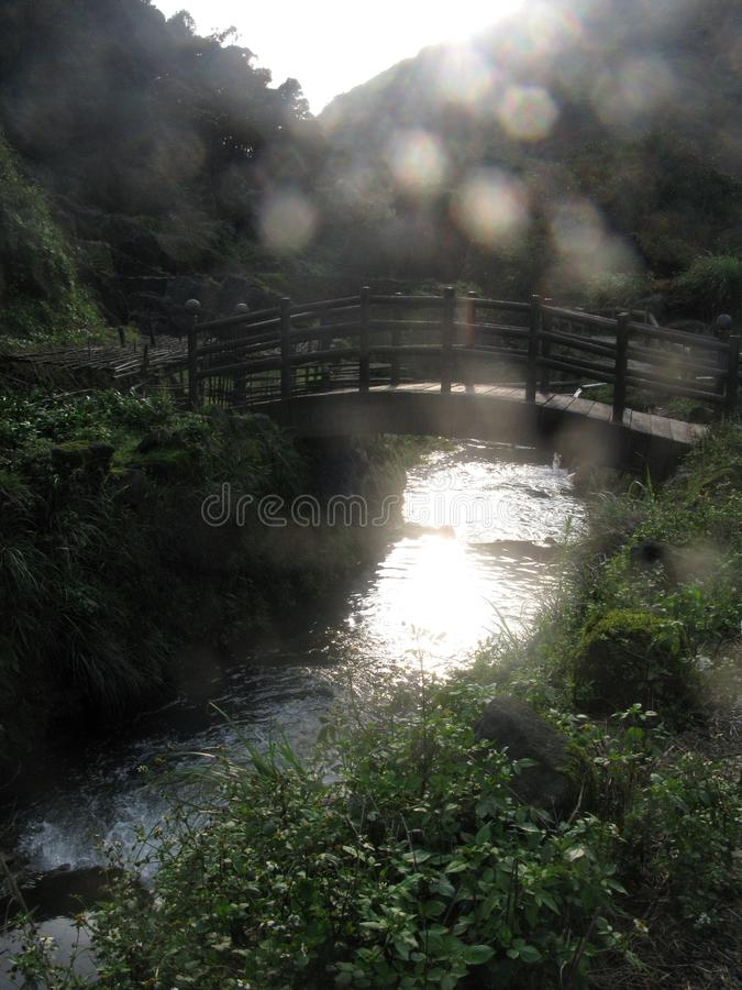 Ξύλινη γέφυρα επάνω από τον ποταμό με την ηλιοφάνεια στοκ φωτογραφία