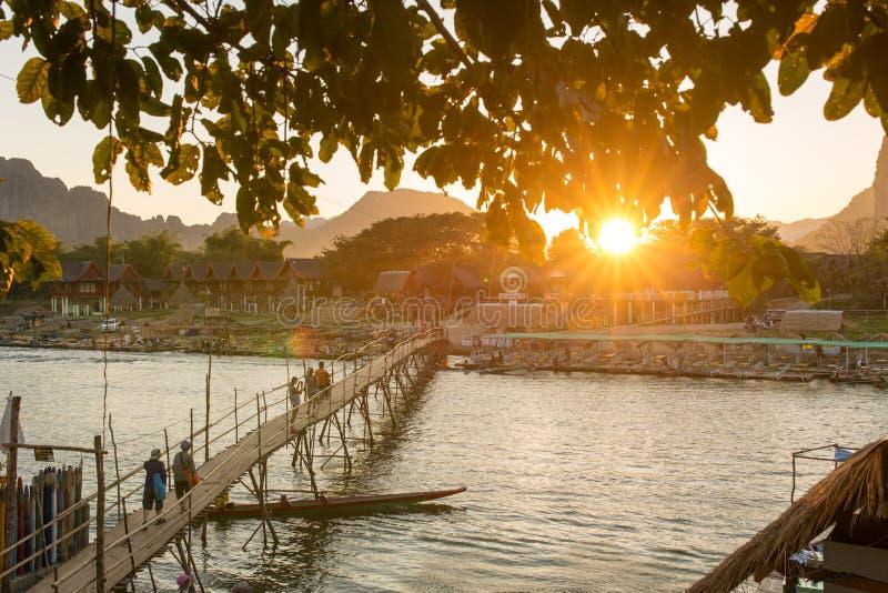 Ξύλινη γέφυρα πέρα από τον ποταμό τραγουδιού Nam κατά τη διάρκεια του ηλιοβασιλέματος στο χωριό Vang Vieng στοκ εικόνες